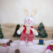 Christmas toy rabbit on background trees — Stock Photo #33497467