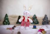 Christmas toy rabbit on background trees — Stock Photo