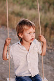Happy young boy playing on swing in a park — Stock Photo