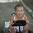 Stock Photo: Driving little girl. Beautiful cheerful