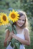 Young pretty woman on a sunflowers — Stock Photo