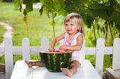 Blonde litle girl eats a slice of watermelon — Stock Photo