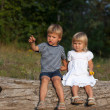 Boy and girl sitting on log — Stock Photo