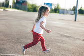 Little girl running away on the road — Stock Photo