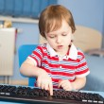 kleine babyjongen te typen op het toetsenbord van de computer — Stockfoto