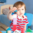 Little baby boy is building with wooden toy blocks — ストック写真