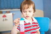 Litlle chlapec hraje s dřevěnými kostkami — Stock fotografie