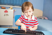 Little baby boy typing on computer keyboard — Stok fotoğraf