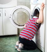 Niño peligrosamente poniendo su cabeza en la lavadora de tambor — Foto de Stock