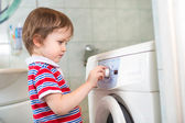 Little baby boy programming washing machine in bathroom — Stock Photo