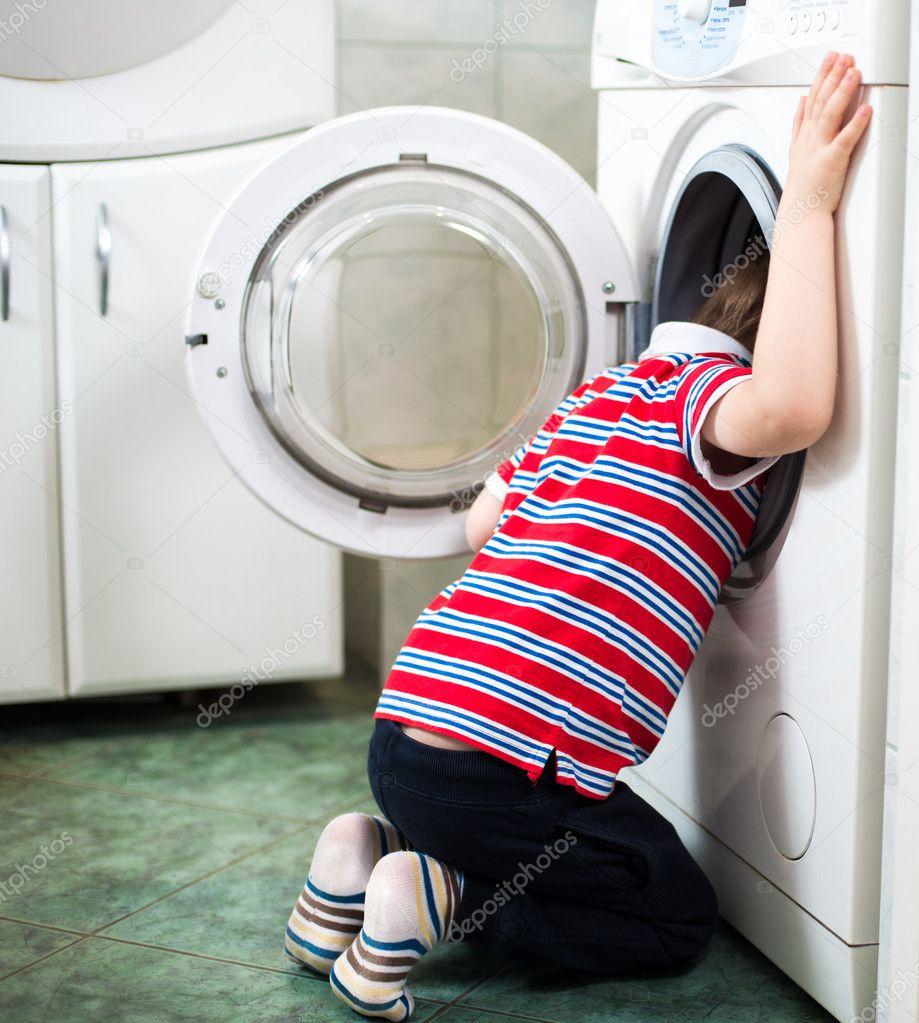 Liten pojke farligt att sätta huvudet i tvättmaskin trumma ...