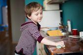 Boy cleaning the kitchen — Stok fotoğraf