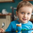 Little three year old boy eats an egg — Stock Photo