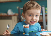 Small happy three year old boy eats an egg — Stock Photo