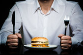 Hamburger on a plate in front of a man — Stock Photo