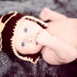 Stock Photo: Newborn baby in small pilot cap lying on blanket