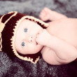 Newborn baby in a small pilot cap lying on blanket — Stock Photo