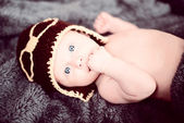 Newborn baby in a small pilot cap lying on blanket — Stockfoto