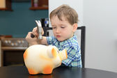 4 year old boy is preparing to break the piggy bank — Stock Photo