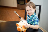 4 year old boy wants to break the piggy bank — Stock Photo