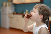 4 year old boy eats chocolate muffin — Stock Photo