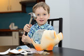 4 year old boy satisfied with breaking the piggy bank — Stock Photo