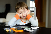 Worried 4 year old boy sitting at the table with medications — Stock Photo