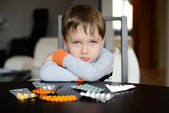 Sad preschooler sitting at the table with pills — Stock Photo