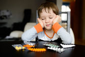 Sad 4 year old boy sitting at the table with pills — Stock Photo
