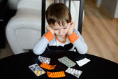 Sad 4 year old boy sitting at the table with medications — Stock Photo