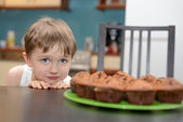 4 year old boy hungrily looking at chocolate cake — Stock Photo