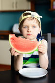 4 year old boy in a cap eats a watermelon at the kitchen table — Stock Photo