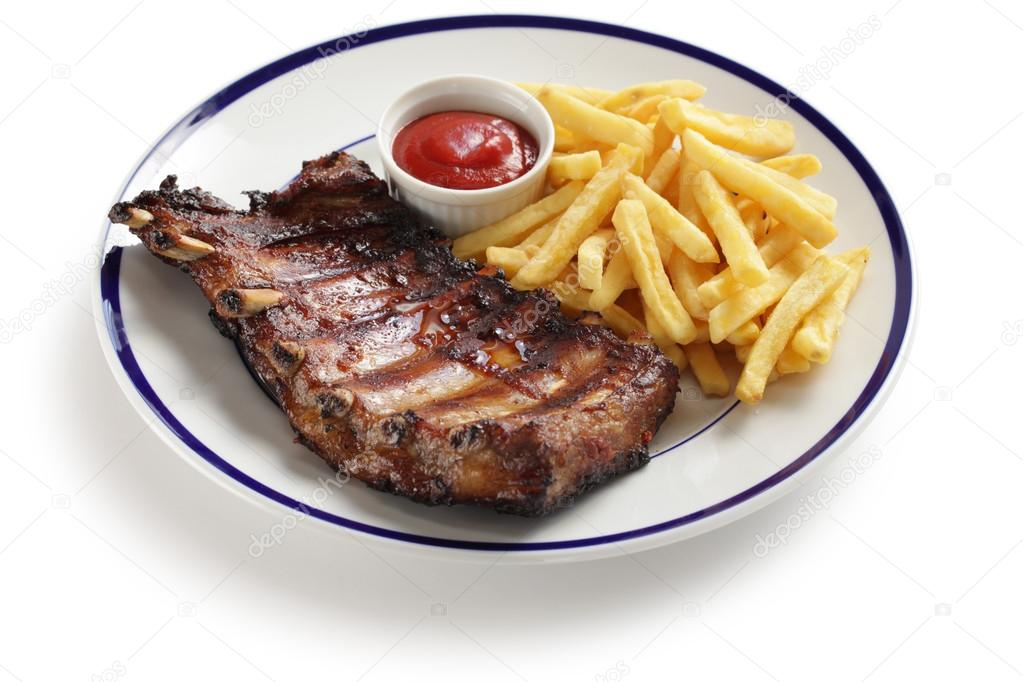 A rack of cooked pork spare ribs and french fries  Stock Photo #13708328