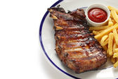 Barbecued pork spare ribs and french fries — Stock Photo