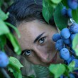 Stock Photo: Beautiful young womeating grapes – focus on grapes