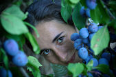 Beautiful young woman eating grapes – focus on grapes — Stock Photo