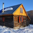 Small cabin in the mountains at winter - Stock Photo