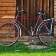 Vintage red bicycle near a wooden house — Stock Photo
