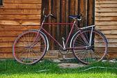 Vintage bicycle rouge près d'une maison en bois — Photo