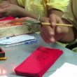 Old woman write chinese letters on a paper — Stock Video