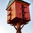 Wooden birdhouse on a wooden post in the outdoors — Stock Photo