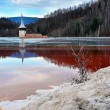 Stock Photo: Flooded church in toxic red lake. Water polluting by copper mine