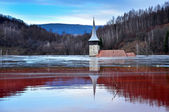 A flooded church in a toxic red lake. Water polluting by a copper mine — Stock Photo