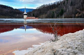 A flooded church in a toxic red lake. Water polluting by a copper mine — Stockfoto