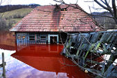 Ecological disaster. A house flooded by contaminated water from a copper open pit mine — Stock Photo