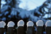 Wooden fence in winter with snow and ice crystals on top — Stockfoto