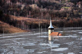 Abandoned church in a mud lake. Natural mining disaster with wat — Stock Photo