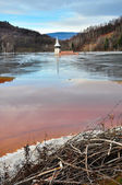 A flooded church in a toxic red lake. Water polluting by a coppe — Stock Photo
