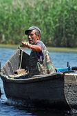Fisherman in a boat in the Danube delta, Romania — Stock Photo