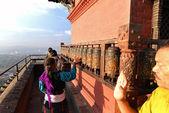 Buddhist pilgrims circling around the Swayambhunath temple and s — Stock Photo